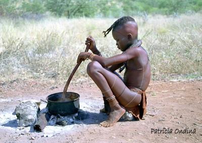Petite fille himba préparant à manger